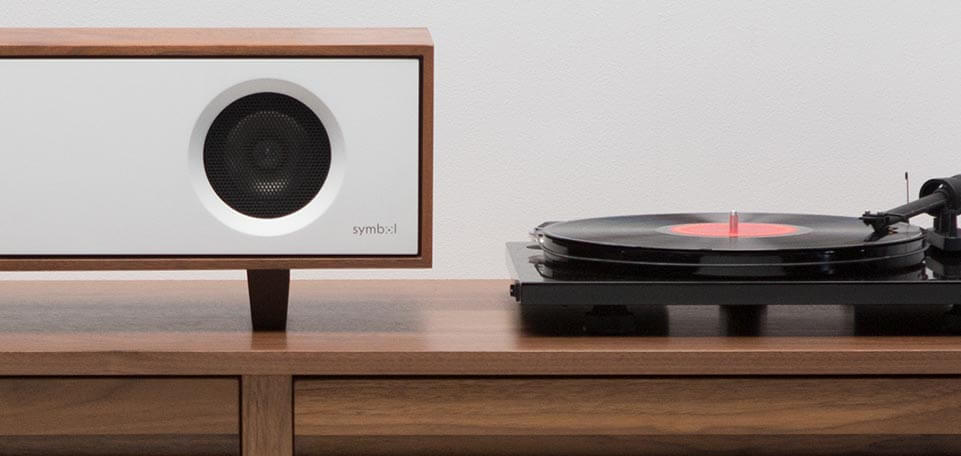 Tabletop Hifi speaker with a dark natural walnut finish. Crafted with North American hardwoods. It sits at 28.75 inches wide and 9.5 inches tall and weighs 30 lbs. It is displayed on a cabinet next to a record player.
